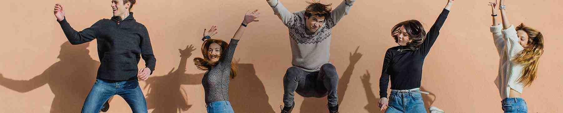 Une photo prise au bon moment d'un groupe d'amis sautant avec leurs mains en l'air