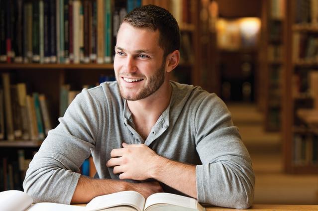 Un homme à la librairie souriant avec des livres sur sa table.