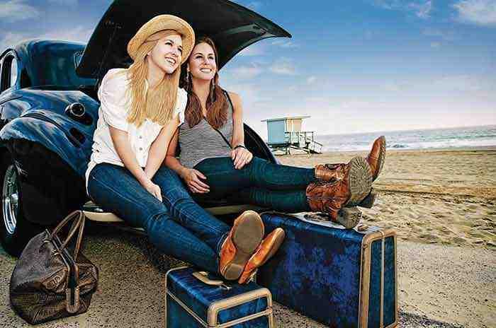 Deux filles assissent dans le coffre d'une voiture près de la plage avec valises prêtes à partir en vacances.