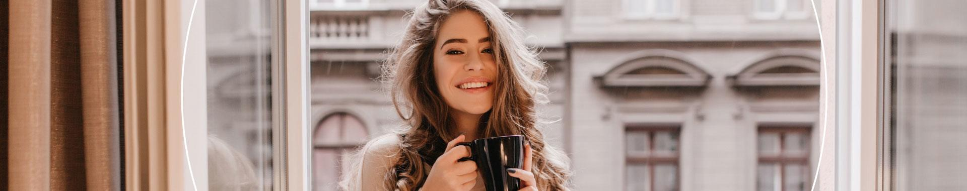 Woman standing in window with a hot drink in hand, smiling.
