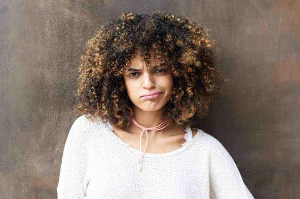 Image d'une femme avec une expression faciale non impressionnée.