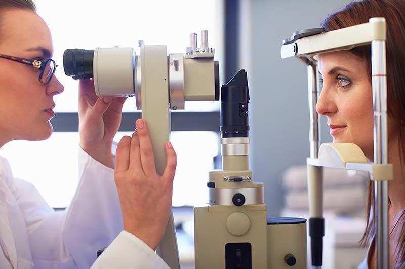 Une vue de côté d'une ophtalmologue et une jeune femme regardant à travers une caméra rétinienne