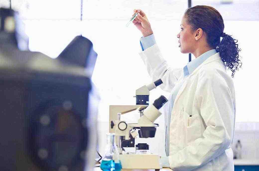Un médecin en laboratoire qui regarde à travers un tube à essai.