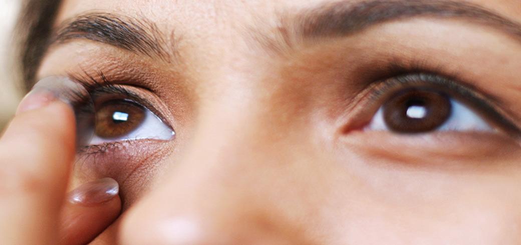 Un plan serré sur une femme regardant dans un miroir et pour mettre ses lentilles de contact